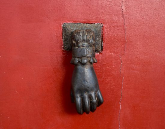 A small, black hand shaped knocker on a cracked red door.
