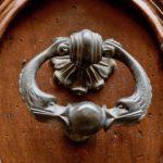 Two silver fish kiss a door knocker handle on a dark brown door.
