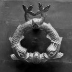 Two silver colored fish creating a circle door knocker on a black door.
