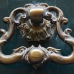 Two bronze ducks kiss a door knocker handle on a dark green door.