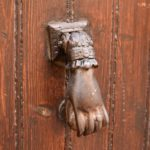 A copper hand door knocker on a dark wooden door.