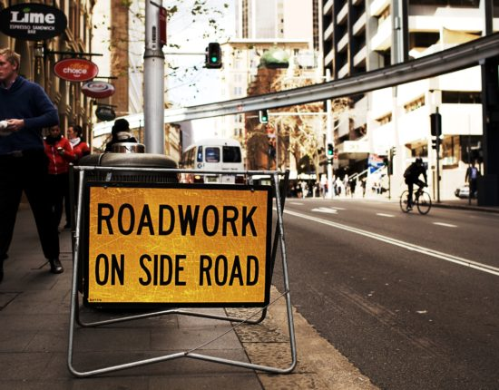 """A man walks behind a construction sign that reads """"ROADWORK ON SIDE ROAD"""" on a busy city street."""