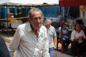 An elderly man is walking and blowing cigarette smoke from the side of his mouth. He is in a button-up shirt and there are people in the background.