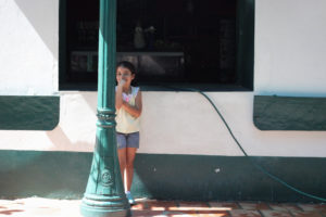 A young girl in shorts and a light top is standing behind a street pole, her hand is shrouding her mouth but she is smiling.