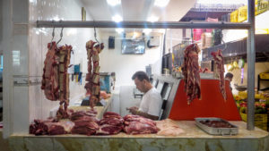 A man is in the background looking at his phone. In the foreground, there are butcher's hooks full of raw meat and there are cuts of meat on the store counter.