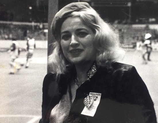 A black and white picture of an older blonde woman smirking at the camera