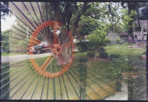Orange steering wheel with thin metal rods sticking out sits along a boarded up window and is faded with a beige house with a large yard and several cars parked in the driveway.