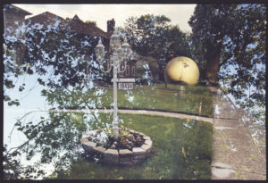 A tree with a whiteish yellow ball is faded behind a dark brown house with a clean cut yard and tall, white yard light.
