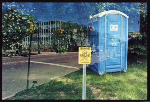 Bright blue portable toilet sits on grass and in front of a tree is faded with a wide teal and black building that sits behind a street with a traffic light on the right side near a yellow 'Gas Pipeline' sign.