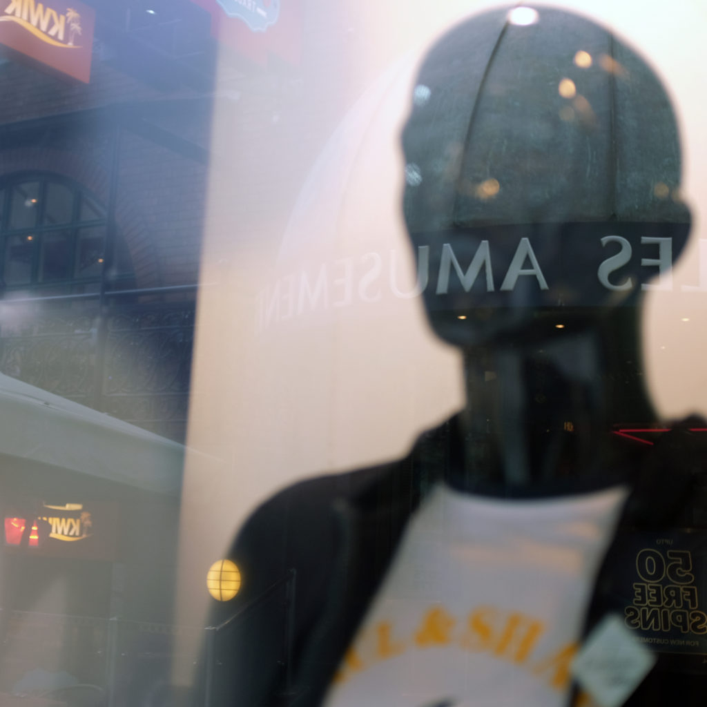 Unrecognizable words are reflected onto a faceless mannequin through a window.