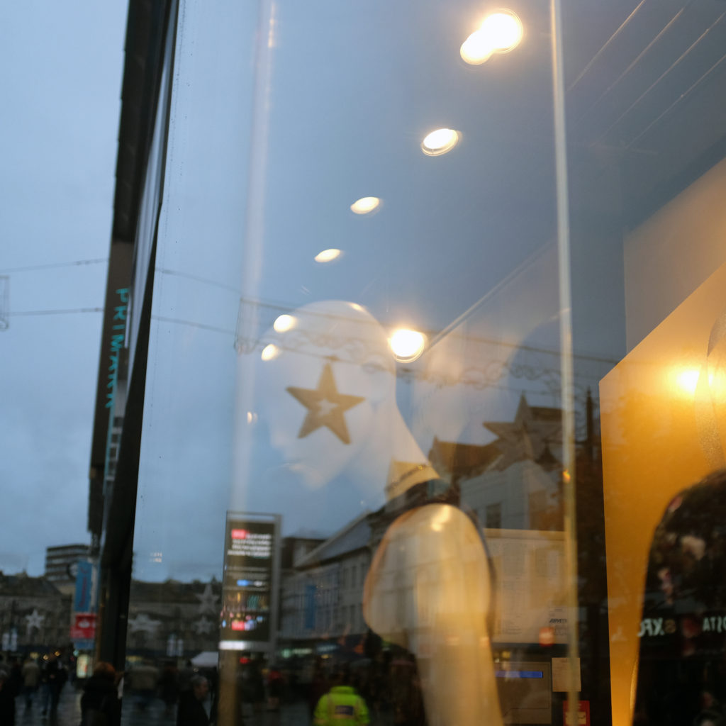 A star is reflected onto a faceless mannequin through a window.