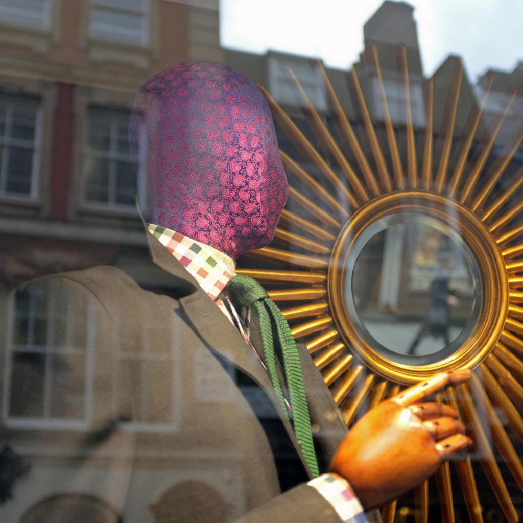 A mannequin with wooden hands stands in front of a sun like mirror. An urban setting can be seen in the reflection of the glass.