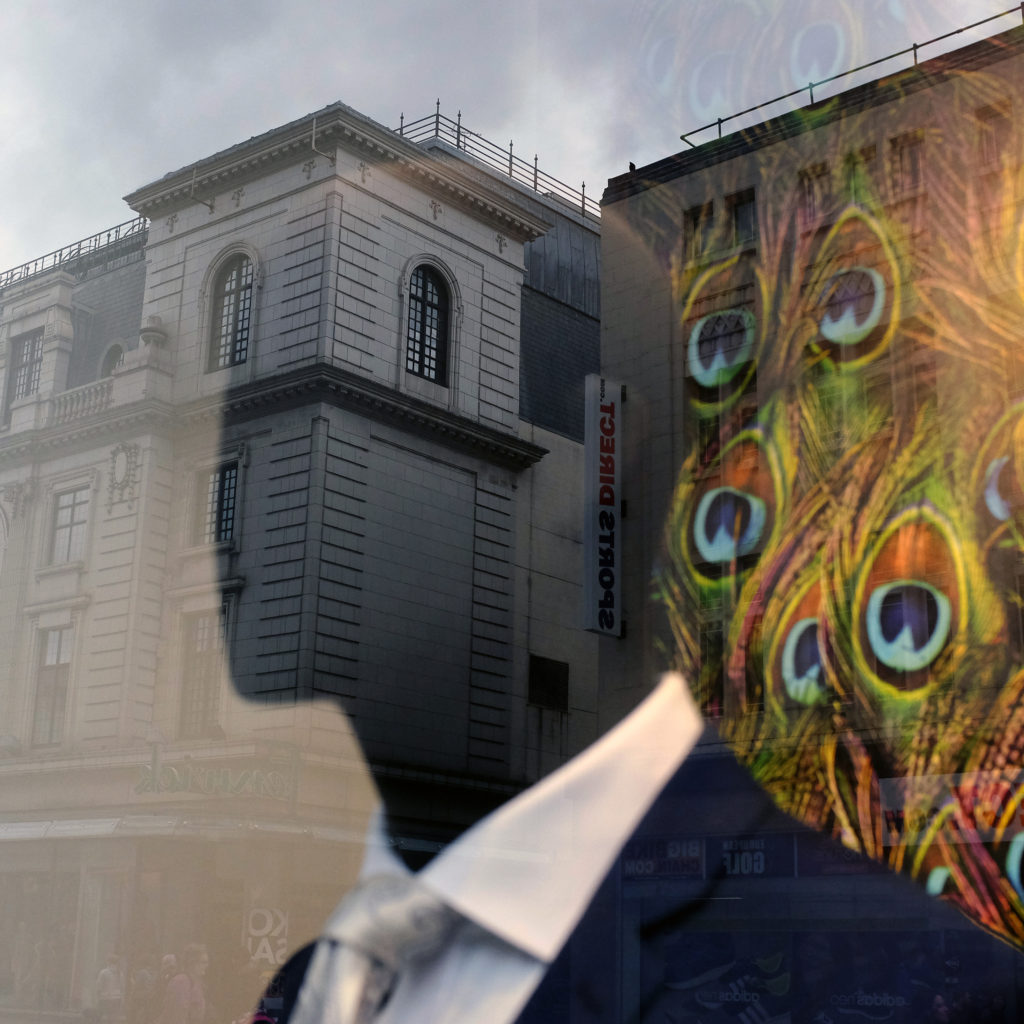 A faceless mannequin in a suit with a peacock background is reflected onto a large, ornate building.