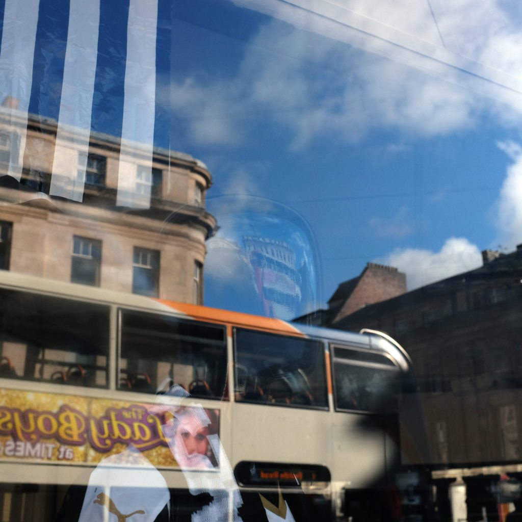 A distorted figure is reflected on a city bus.