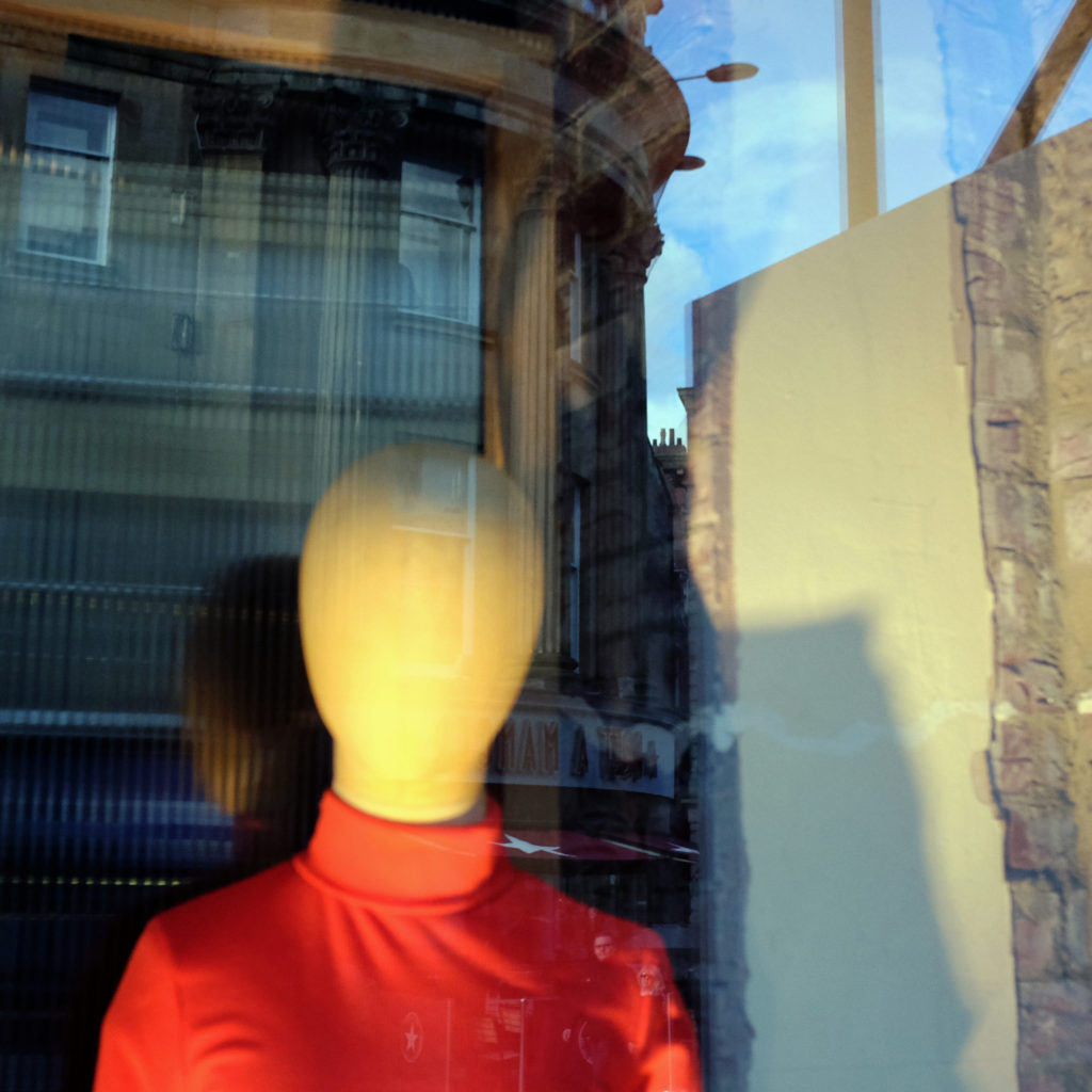 A faceless mannequin in a turtleneck looks out a window where the streets of the urban setting outside reflect onto the glass