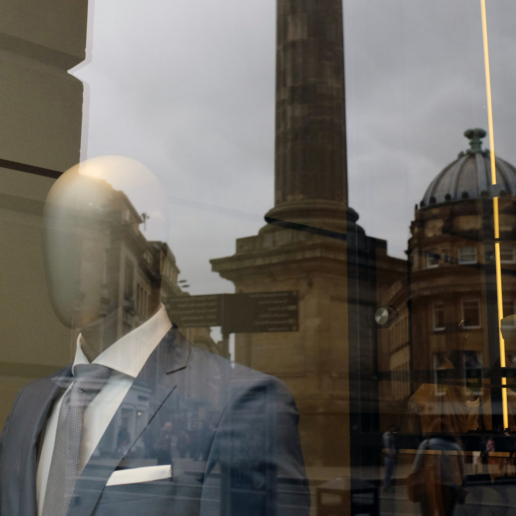 In a store front window, the European city of Newcastle upon Tyne is reflected behind a faceless mannequin dressed in a designer suit jacket with a light gray tie