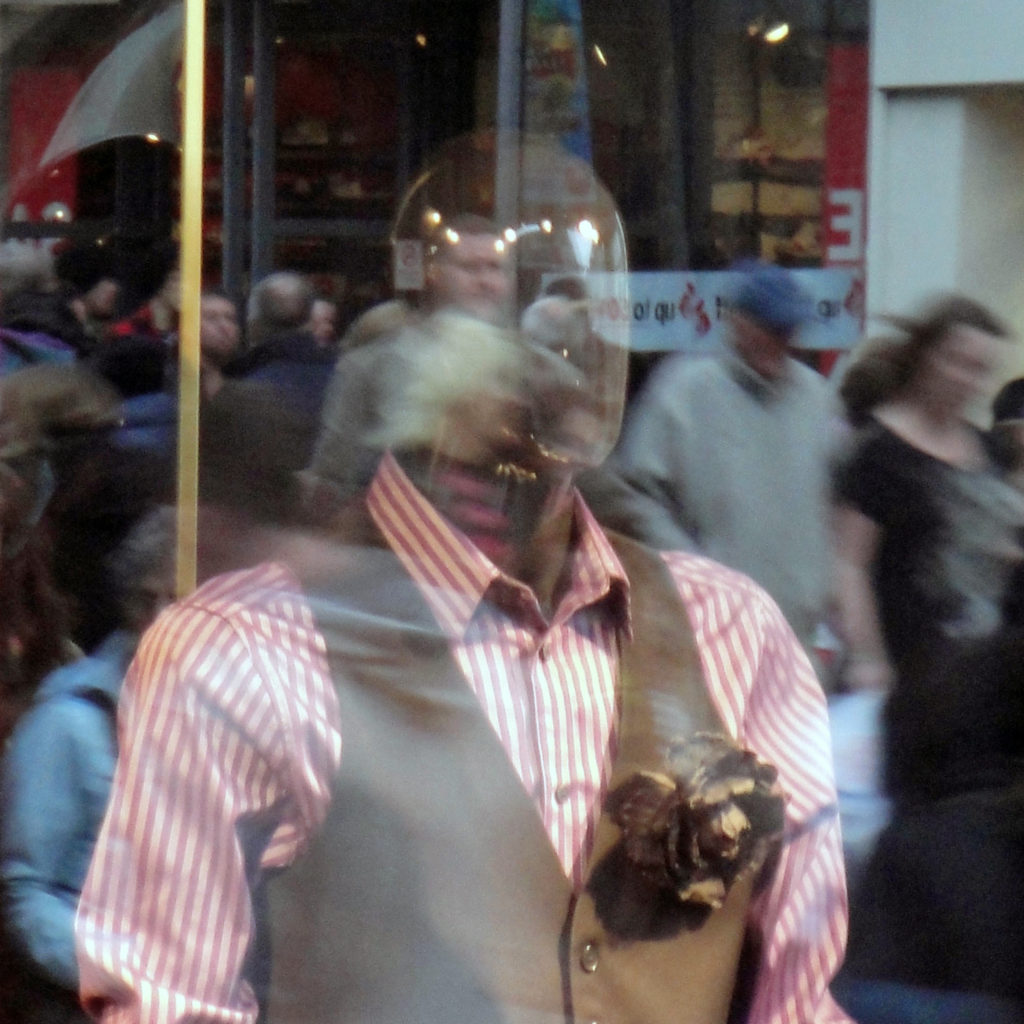 A faceless mannequin in a button up and vest looks out a window where a busy crowd can be seen walking past in the reflection.