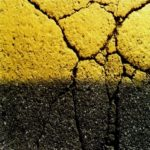 Extreme close up on cracks in a yellow stone. A shadow cuts the stone in half horizontally