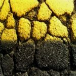 Close up on cracks in a yellow line. The stone is cut in half by a shadow running horizontally.