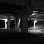 Black and white picture of the underpass of a highway.