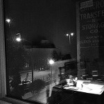Black and white picture taken through a window overlooking a rainy street.