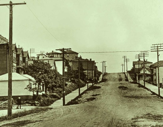Black and white photograph of an empty suburban street.