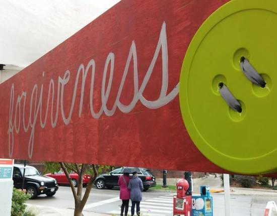 "A bright red sign with a giant yellow button attached, reads ""Sewing Forgiveness."""