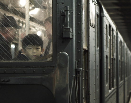 A young boy looks out the window of a train. The rest of the train can be seen behind him, disappearing into the distance.