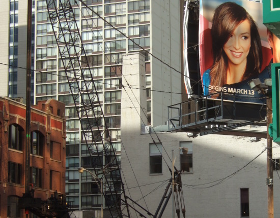 Billboard with a smiling lady overlooks the construction of condominiums.