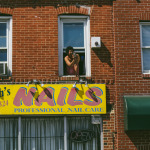 "A person peeks their head out of a second floor window. Below them, a sign reads ""Aaliyah's NAILS."""