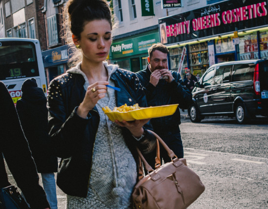 A woman walks down a city street eating out of a takeout box.