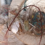 A mass of hair entangled with pieces of yarn.