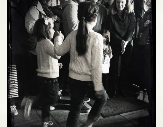 Two young girls in white sweaters hold hands while Irish dancing before a small crowd of adults.