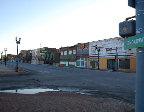 "An empty intersection surrounded by empty brick sidewalks and a row of street lamps in the small town of Gary, Indiana. A street sign in the foreground says ""Broadway"
