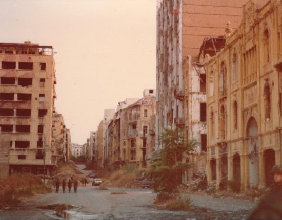 Abandoned buildings in Beirut line a gravel road where there are piles of dirt and several soldiers standing guard.
