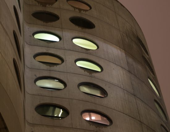 The side of a tall, barrel-shaped building with oval windows.