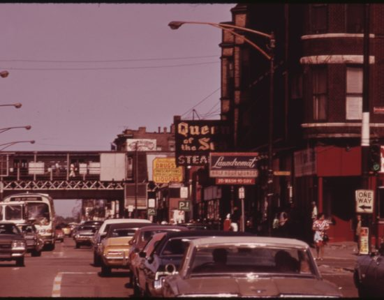 South Side Chicago in 1970. Vintage cars are driving down a road with business marquees on the sidewalks.