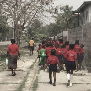 A group of school children walk down a sidewalk with their backs to the camera. The last two (a boy and a girl) hold hands.