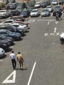 Two men walk through a row in a parking lot.