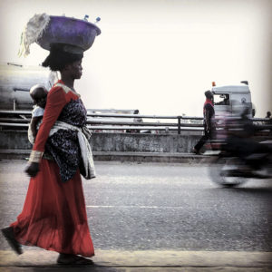 A woman in a red dress with a child tied to her back walks alongside a road. She is balancing a purple basket on her head.