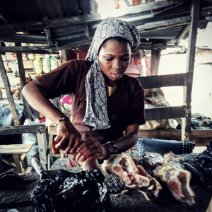 A woman stands in front of some unspecified meat.