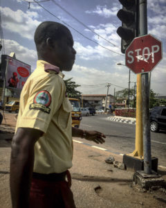 A Lagos State Traffic Management Association walks next to a road and a stop sign.