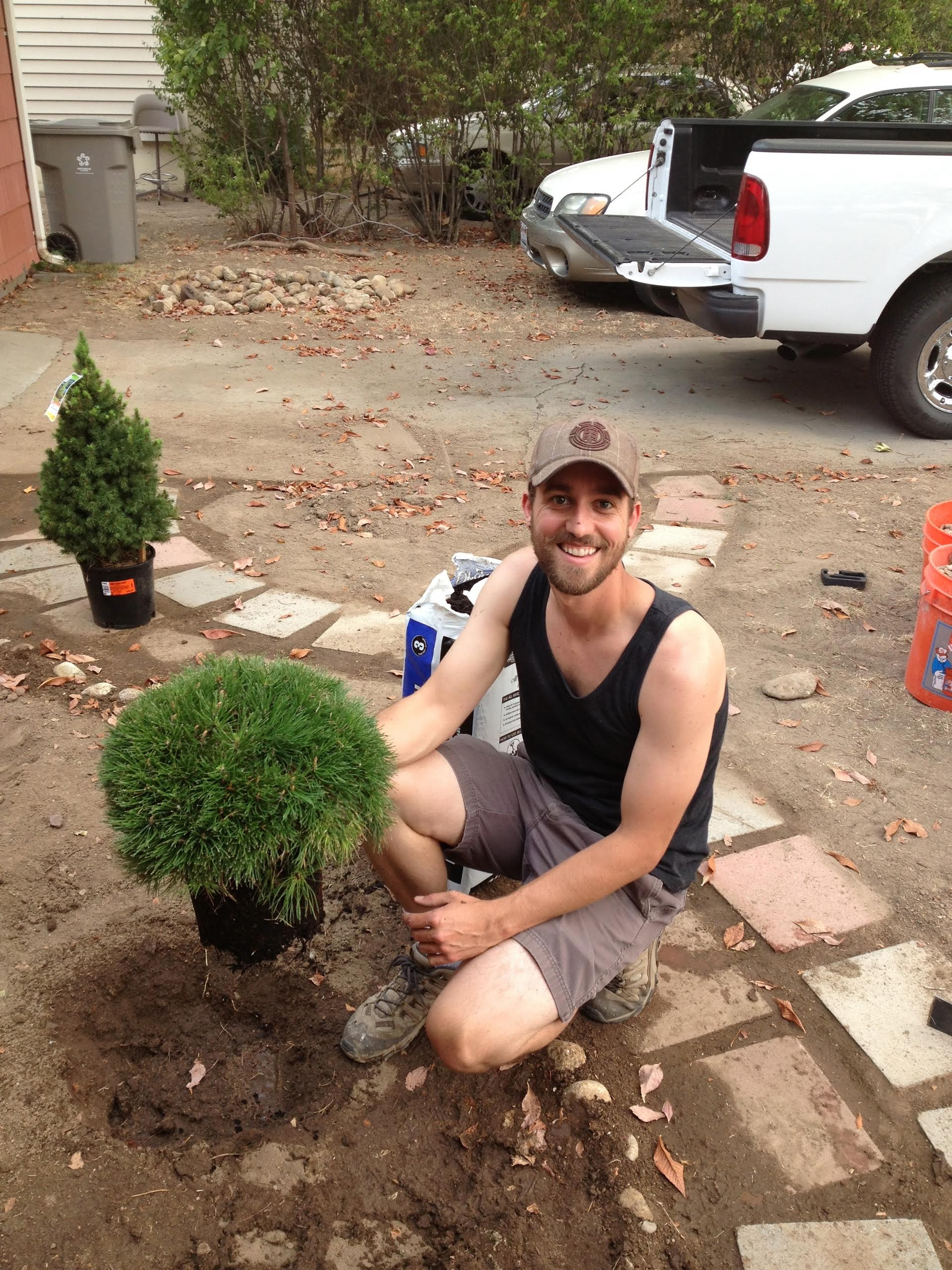 [Author, Kyle Bilinski, smiles while planting a shrub into the soil.]
