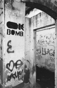 "An doorway is graffitied with a picture of a cartoon atomic bomb and the word ""bomb"" as well as other spray painted words"