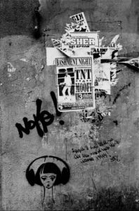 A wall with layers of ripped posters and graffiti of a woman with headphones on and some Italian words.