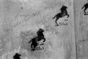 "a wall with the words ""The Four Horseman"" written on it. To the right there are four identical images of spray painted black horses with the words ""MAKE GRAFFITI!"" underneath each."