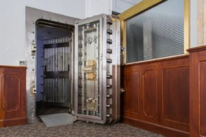 Large metal vault rests open against wooden walls.