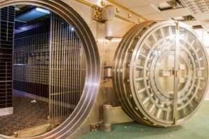 A large, walk-in vault full of empty safety deposit boxes sits open in an unused building, which is soon to transformed for some new architectural use.