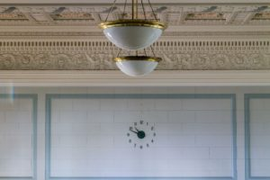 Light fixtures hang in an empty room, partially blocking the crown molding in the background. The clock on the wall reads 10:49.