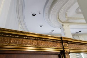 Ornate, golden crown molding sits below a white ceiling.